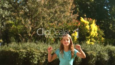 Cute little girl jumping in her garden