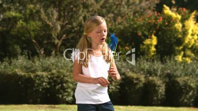 Little girl blowing a pinwheel in her garden
