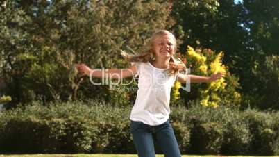 Cheerful little girl jumping in her garden