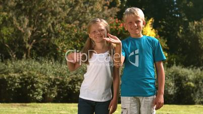 Cheerful siblings waving together in their garden