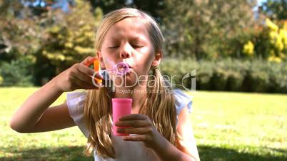 Young girl blowing into a bubble wand