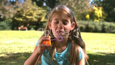 Smiling young girl blowing into a bubble wand