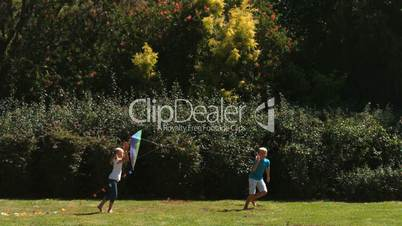 Siblings having fun in a park with a kite