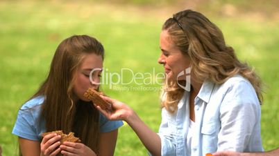 Mother and her daughter eating a sandwich together