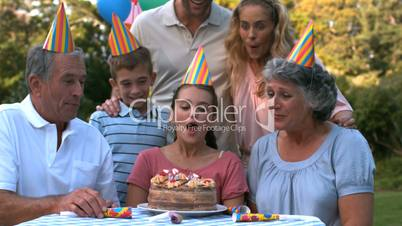 Happy family blowing the candles of birthday cake