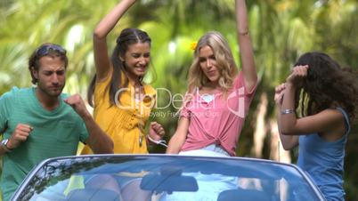 Friends having fun and dancing in the car