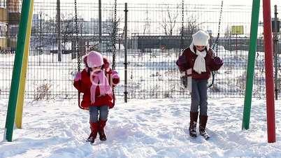 Girls in swings in winter playground