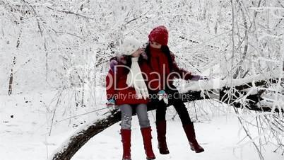 Girls talking on a tree in winter forest