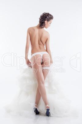 Naked slender bride posing back to camera