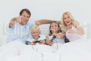Children playing video games in bed