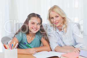 Woman helping her daughter doing her homework