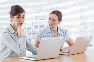 Worried businesswomen working on laptops