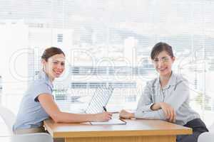 Businesswomen having a meeting at desk and smiling at camera