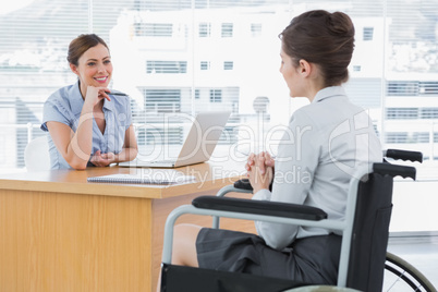 Businesswoman listening to disabled job candidate