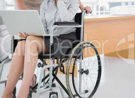 Disabled businesswoman showing laptop to colleague