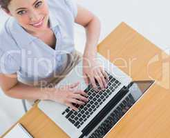 Pretty businesswoman typing on her laptop and smiling up at came
