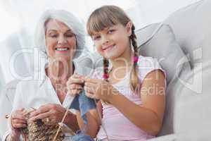 Young girl and her granddaughter knitting together