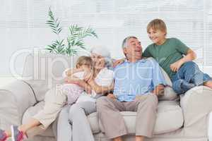 Smiling grandchildren embracing their grandparents