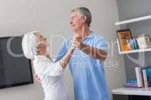Elderly couple dancing in the living room