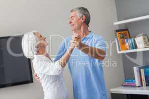 Elderly couple dancing in the living room