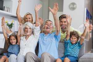 Multi-generation family raising their arms