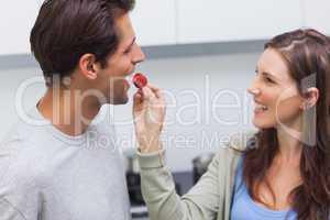Woman feeding her husband cherry tomato