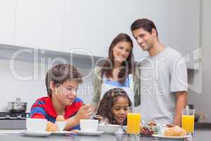 Children having breakfast in kitchen