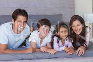 Cheerful family lying on bed