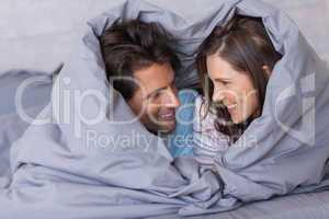 Cheerful couple having fun wrapped in their duvet