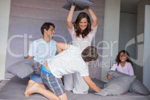 Family having a pillow fight on the bed