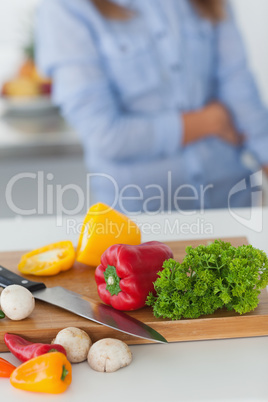 Wooden board with vegetables on a kitchen table