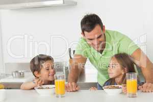 Father chatting to his children while they are having breakfast