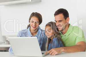 Family using a laptop on the kitchen table