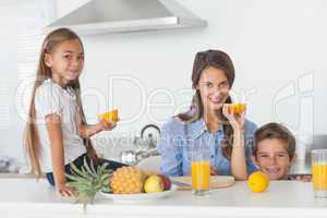 Siblings raising a half orange in the kitchen