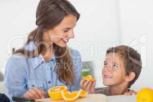 Little boy eating orange segments