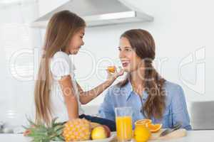 Little girl giving an orange segment to her mother