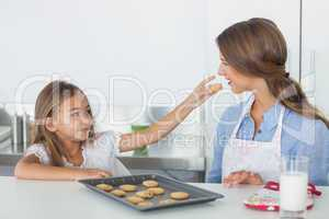Little girl giving a cookie to her mother