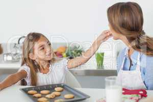 Young girl giving a cookie to her mother