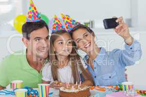 Woman taking pictures of her family during a birthday party