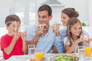 Happy family eating pizza slices