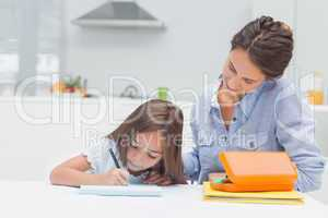 Mother looking at her daughter drawing