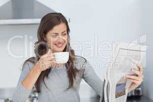 Woman with a cup of coffee reading a newspaper