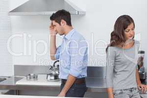 Couple sulking at each other in the kitchen
