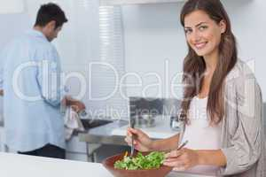 Woman mixing a salad in the kitchen