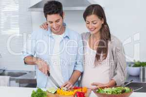 Man cutting vegetables next to his preganant partner