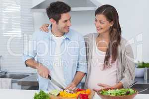 Man chopping vegetables next to his pregnant partner