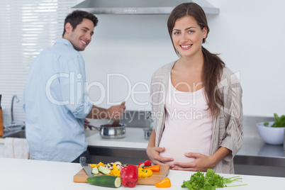 Cheerful pregnant woman holding her belly in the kitchen