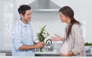 Man giving flowers to his pregnant partner