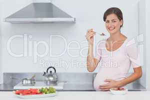 Pregnant woman eating cereal in the kitchen