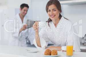 Woman with a dressing gown having breakfast